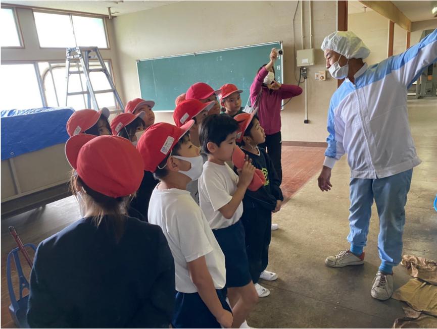 薬草農園内を見学する小学生へ説明する職員